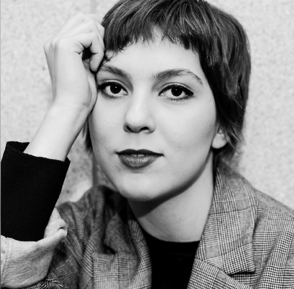 Black and white portrait of the artist, Amanda Gatti with short hair, with their hand resting on the left side of their head. wWearing a blazer and black top.